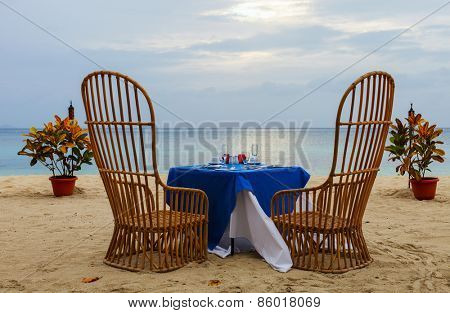 Romantic dinner setting at tropical beach on sunset