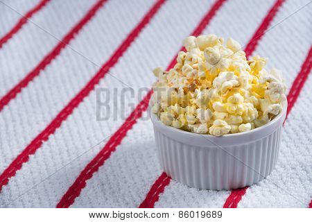 Closeup of a Ramekin Full of Popcorn on a White and Red Background.