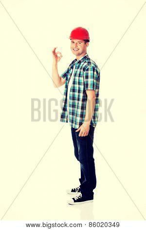 Portrait of a builder in a white helmet gesturing OK