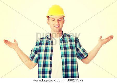 Happy in helmet worker presenting copy space.