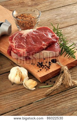 Raw prime rib beef steaks with spices, garlic and rosemary. Also available in horizontal.