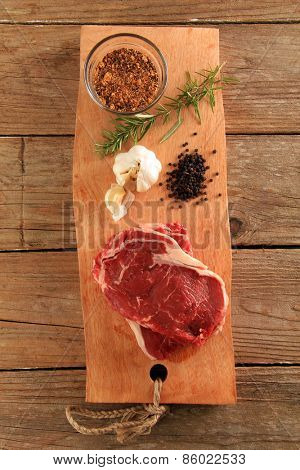 Raw prime rib beef steaks with spices, garlic and rosemary.
