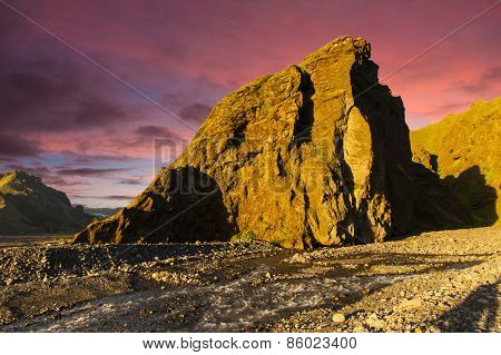 Midnight setting sun shines on beautiful volcanic rocks at Thorsmork, Iceland