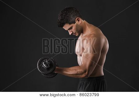 Portrait of a muscular man lifting weights against a dark background