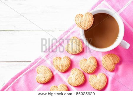 Cup of coffee and heart shaped cookies on pink dishtowel