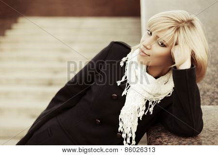 Young fashion blond woman in black coat daydreaming on the steps