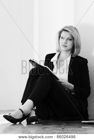Young fashion business woman with a folder sitting at the wall