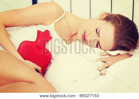 Close up of woman with hot water bottle in bed.