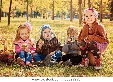 Four Happy Children Playing In Autumn Park With Fruits