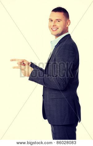 Happy man in suit showing copy space with his hand