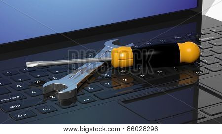 Screwdriver and wrench on laptops keyboard