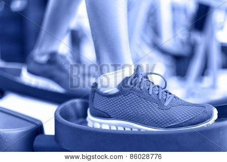 Cardio exercise - Elliptical workout machine in gym. Closeup of female feet using equipment at the fitness center for working out the legs. Sports and recreation concept in Blue monochrome filter.