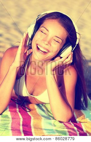 Woman listening to music with headphones at beach. Young Asian girl relaxing during summer holidays lying down with towel on golden sand enjoying her vacations singing happy.