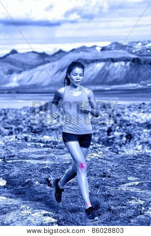 Sports woman portrait showing joints injuries. Active fitness lifestyle can cause ankle and knee sprains showed by red circles on body of female trail runner in nature. Blue monochrome filter.