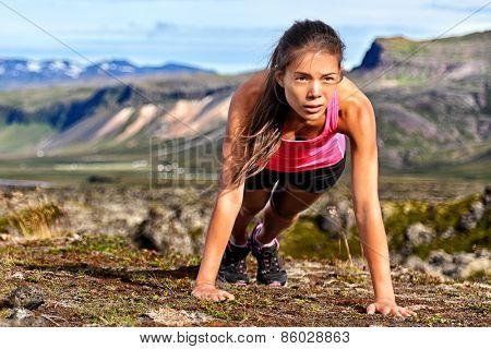 Fitness push-ups woman doing pushups outdoors in nature background. Focused female athlete showing determination and endurance exercising muscles during body core crossfit workout in summer landscape.