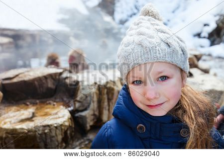 Little girl at Snow monkey Japanese Macaque park looking at monkeys bathe at onsen hot springs in Nagano, Japan