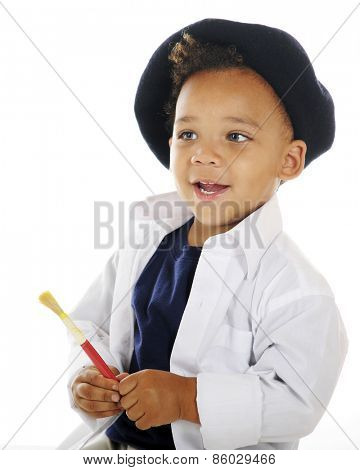 Closeup portrait of an adorable preschool artist holding a paint brush while wearing a white smock and French beret.  On a white background.