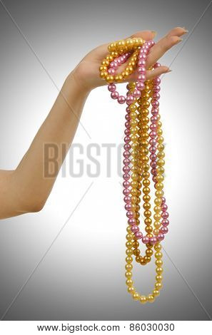Pearl necklace in hand on white
