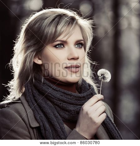 Blond fashion woman with dandelion walking in a forest