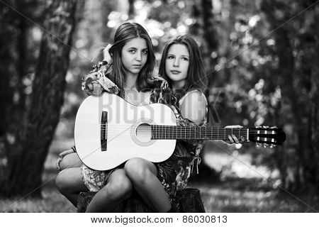 Two young fashion girls with guitar in a summer forest