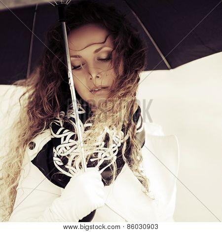 Sad beautiful fashion woman with umbrella