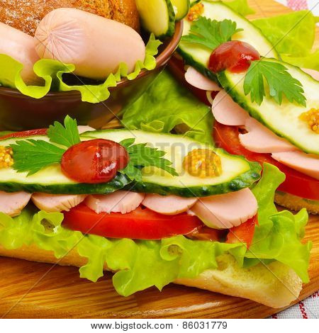 Big Appetizing Fast Food Baguette Sandwich With Lettuce, Tomato And Frankfurter On The Board. Junk F