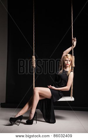 Beautiful girl in black dress on swing.