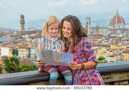 Happy Mother And Baby Girl Looking At Map Against Panoramic View