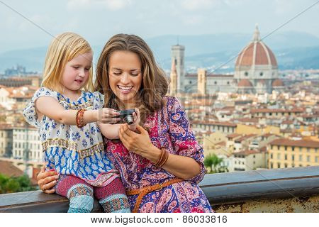 Happy Mother And Baby Girl Checking Photos In Camera Against Pan