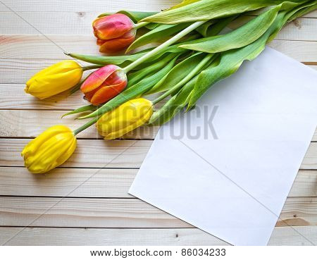 Yellow and orange tulips on a wooden table