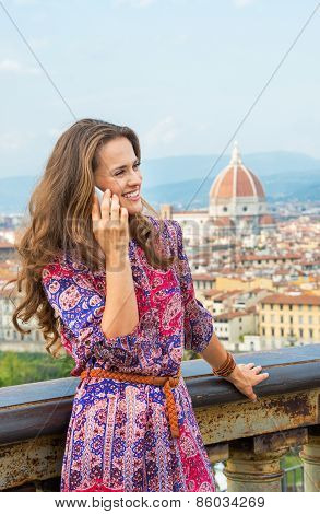 Happy Young Woman Talking Mobile Phone Against Panoramic View Of Florence, Italy