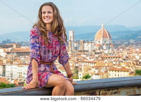 Happy Young Woman Sitting Against Panoramic View Of Florence, Italy