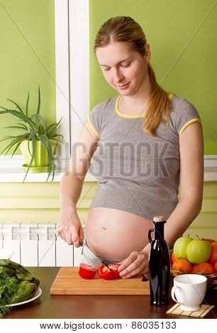 Pregnant woman on kitchen cooking healthy food