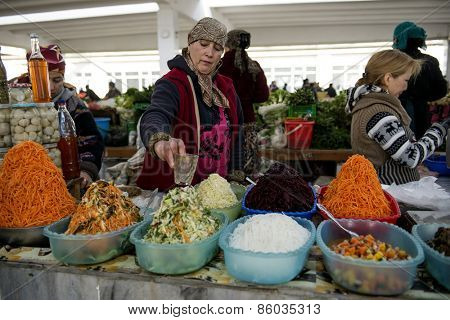 SAMARQUAND, UZBEKISTAN - MARCH 14, 2015: City grocery market.  Man sells pickled carrots and cabbage.