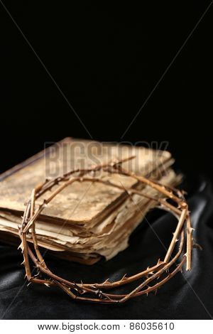 Crown of thorns and old bible on black background