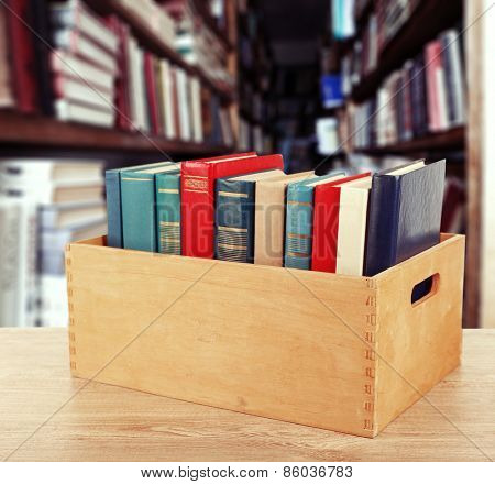 Books in wooden crate on bookshelves background