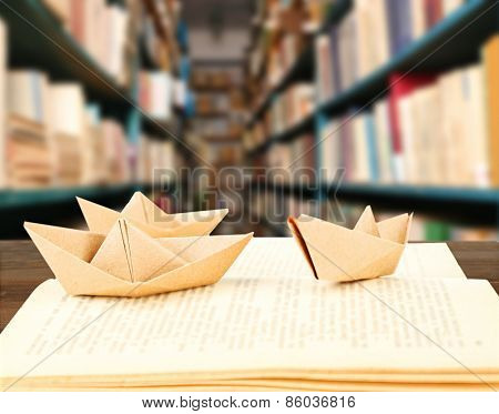 Open book with paper ships on bookshelves background