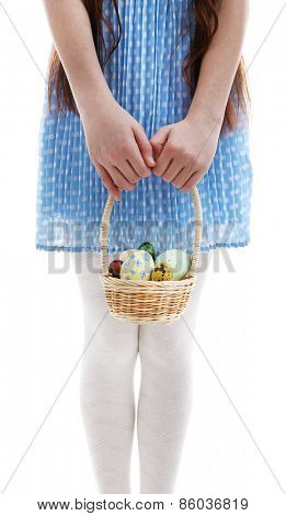 Beautiful little girl holding wicker basket with Easter eggs, close-up, isolated on white