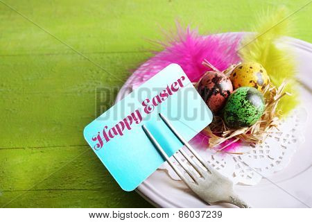 Easter table setting with card and Easter eggs on wooden background