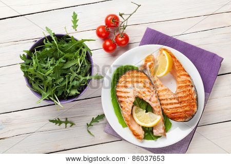 Grilled salmon and salad on wooden table. Top view