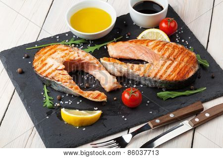 Grilled salmon and spices on stone plate over wooden table