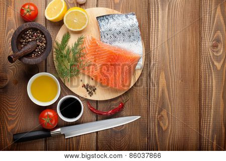 Salmon and spices on wooden table. Top view with copy space
