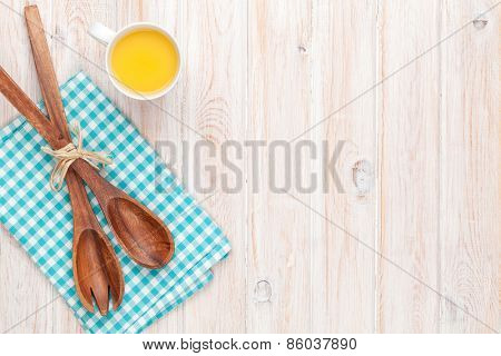 Cup of orange juice and kitchen utensil on white wooden table with copy space