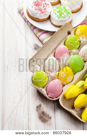 Easter with yellow tulips, colorful eggs and traditional cakes over white wooden table. Top view with copy space