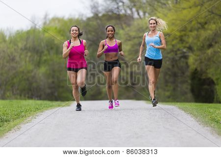 Three young women jogging in a park