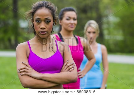 Three young women exercising at a local park