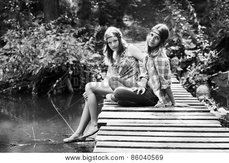 Two young fashion teen girls in a summer forest