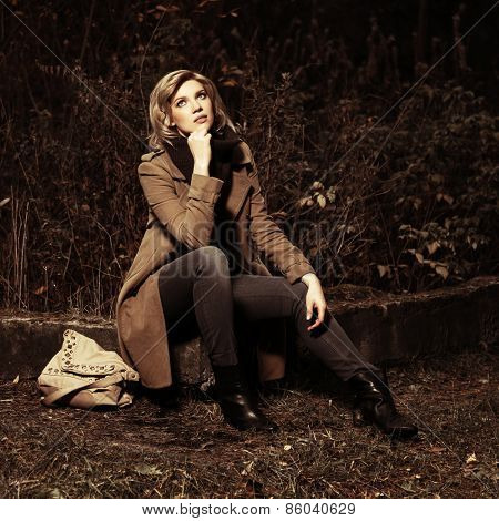 Young blond fashion woman with handbag in autumn forest