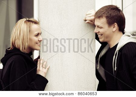 Happy young fashion couple flirting on a city street