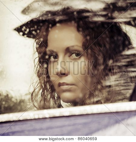 Sad woman looking out car window